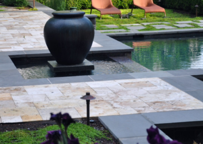 Travertine pavers with bluestone pool coping drop face outdoors