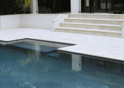 White travertine pool coping with a bullnose
